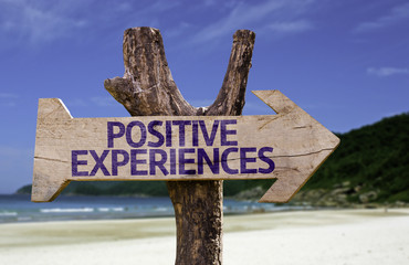 Positive Experiences wooden sign with a beach on background