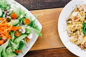 Pasta and salad on wooden table