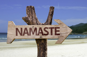 Namaste wooden sign with a beach on background