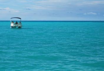A single pontoon boat in a calm tropical sea