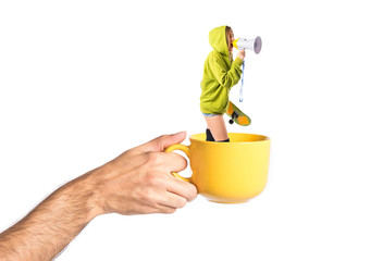 Young girl shouting inside cup of coffee