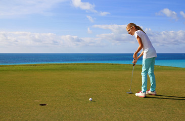 Young Girl Putting a Golf Ball on a sunny day