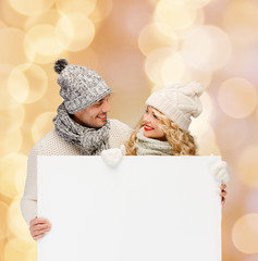 smiling couple in winter clothes with white board