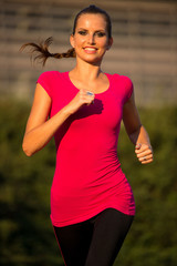 Preety young woman running on a track