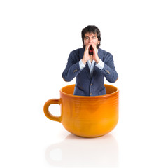 Handsome man shouting  inside cup of coffee