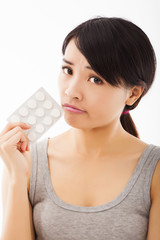 closeup of confused young woman holding pills