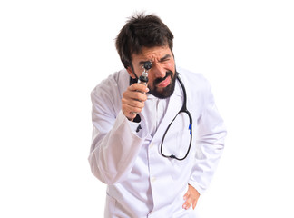 Otorhinolaryngologist with his otoscope over white background