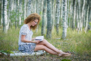 Beautiful woman reading book in forest