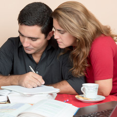 Adult hispanic couple studying or doing office work at home