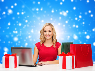 smiling woman in red shirt with gifts and laptop