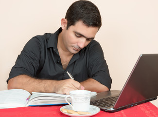 Hispanic man studying or doing office work at home