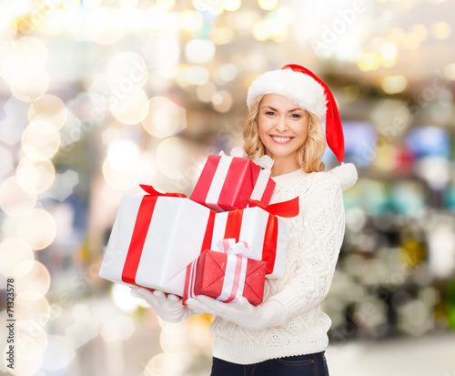 canvas print picture smiling young woman in santa helper hat with gifts