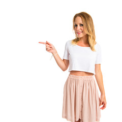 Blonde woman pointing to the lateral over white background