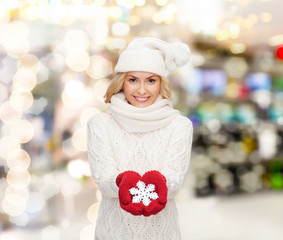 smiling woman in winter clothes with snowflake