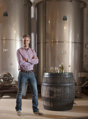 Professional winemaker, looking at camera, in his cellar with mo