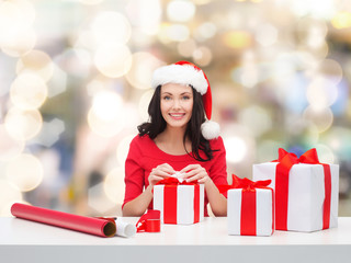 smiling woman in santa helper hat packing gifts