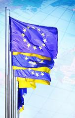 Ukraine and EU flags waving on blue sky.