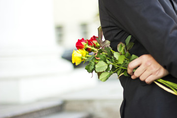man in a black suit  with a bouquet of roses in hands