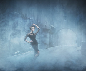 Young and emotional woman in fashion dress on the smoke