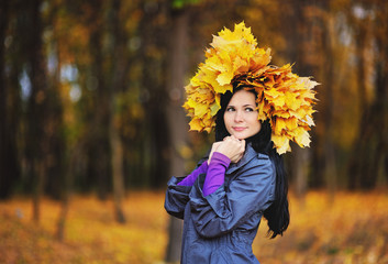 girl with a wreath from yellow leaves on the head on the backgro