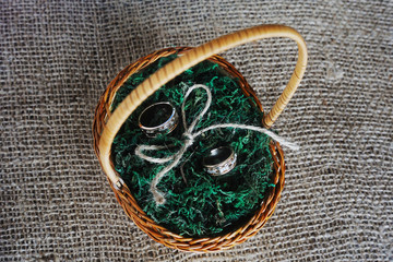 wedding rings in a basket made of straw