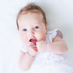 Blue eyed baby girl in a white dress