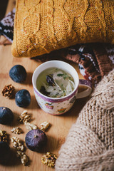Cup with herbal tea and sweaters, figs and nuts