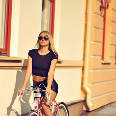 Outdoor fashion portrait of a beautiful blonde model with bike