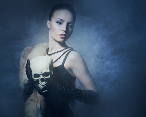 Attractive young lady with a scull on a smoky background
