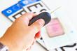 Hand mit Autoschlüssel, im Hintergrund Kennzeichen mit Papiere