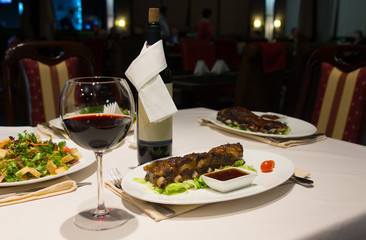 Glass of Red Wine on Table with Plates of Ribs