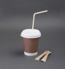 Clotheded take-out coffee with cup holder on gray background.