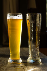 Glass of Beer Beside Empty Glass on Table