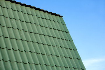 Country house roof from green metal tile against blue sky