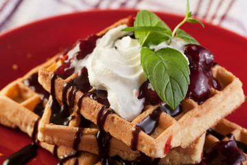 Waffles with chocolate sauce, whipped cream and confiture