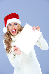 Young woman in a Santa Hat with a blank sign