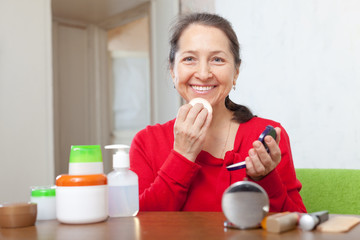 mature woman  putting facepowder on  face