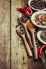 Three wooden spoons with spices and chili peppers