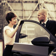 Young fashion business couple talking at the car