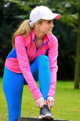 Junge Frau in Sportkleidung bindet ihren Schuh zu