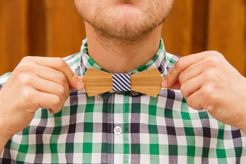 Fashion young man correcting his casual wooden bowtie