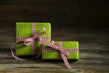 Zwei grüne Geschenke auf Holz mit rot weiß karierter Schleife