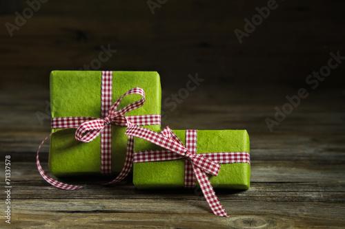 canvas print picture Zwei grüne Geschenke auf Holz mit rot weiß karierter Schleife