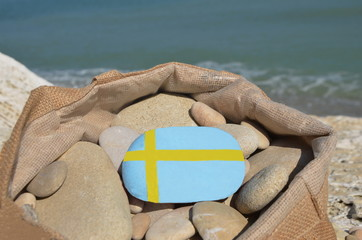 Swedish flag on a stone in a bag with pebbles