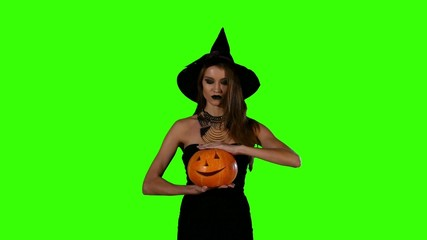 Halloween witch holding a orange pumpkin on green screen