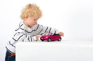 Blonder Junge mit Spielzeugauto