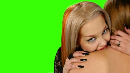 Closeup of a redheaded vampire biting innocent girl on green