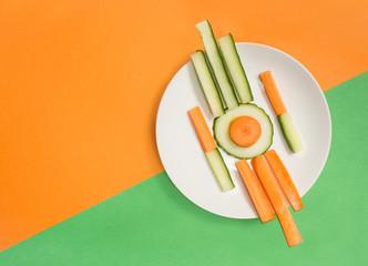 Teller mit Gemüsesticks auf orange-grünem Untergrund