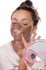 young woman enjoys applying face mask