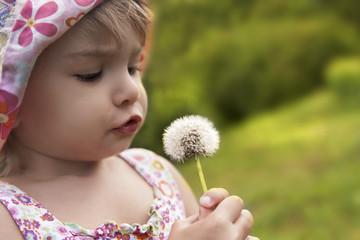 Kid Blowing On A Dandelion